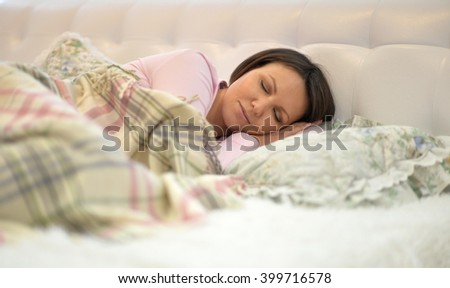 woman sleeping on a white bed - stock photo