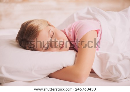 Woman sleeping. Side view of beautiful young woman lying in bed and keeping eyes closed while covered with blanket - stock photo