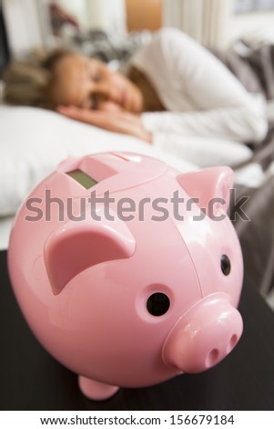 Woman sleeping while her savings are secure in a traditional piggy bank.