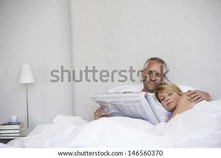 Woman sleeping with man reading newspaper while lying in bed at home - stock photo