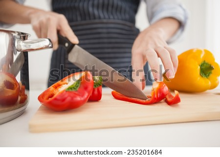 Woman slicing up red pepper at home in the kitchen