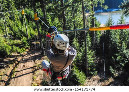 Woman sliding on a zip line in an adventure park - stock photo