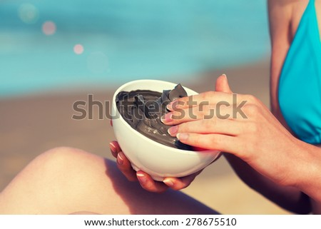 Woman smearing mud mask on the body on the beach - stock photo