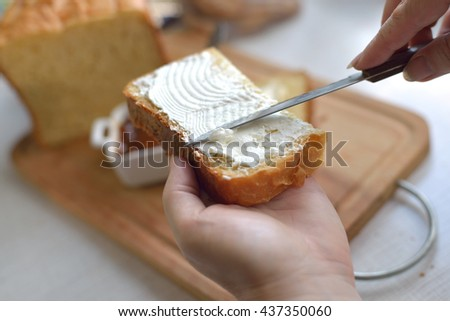 Woman smears bread butter and jam. Macro shot selective focus