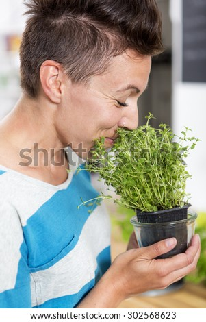Woman smelling on a plant of fresh thyme. She is holding the plant in her hands.