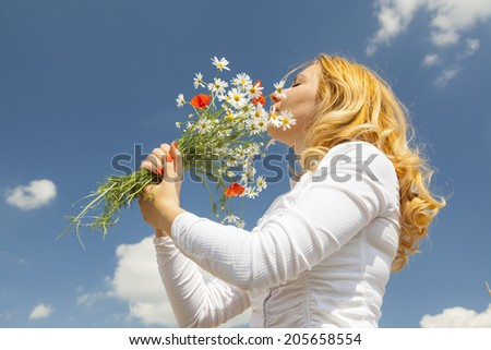 Woman smelling the flowers into the sunlight during summer