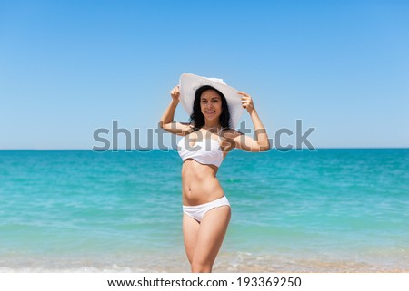 woman smile beach ocean, excited wear white hat and bikini swimsuit, young girl summer vacation holiday on sea enjoying sunny day blue sky - stock photo