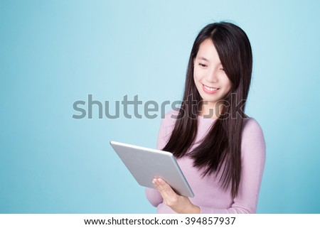 woman smile use tablet pc isolated on blue background, asian beauty