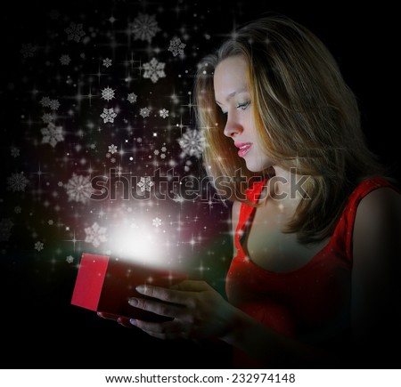 woman smiles and holding a gift in magic packing on a black background - stock photo
