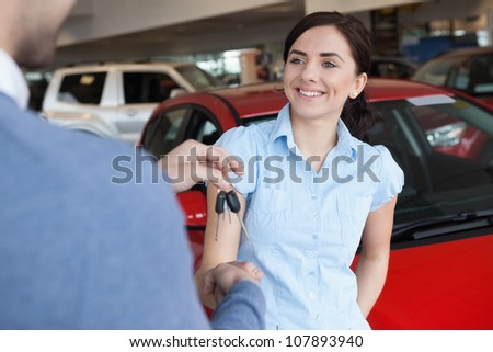 Woman smiles as she shakes someone hand in a car shop