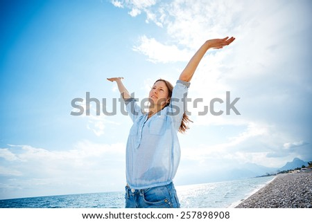 woman smiling  against blue sky looking at the camera - stock photo