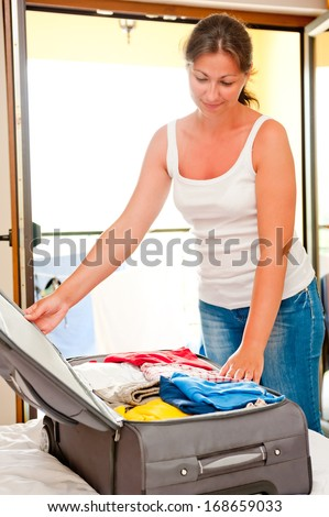 woman smiling and closes the suitcase