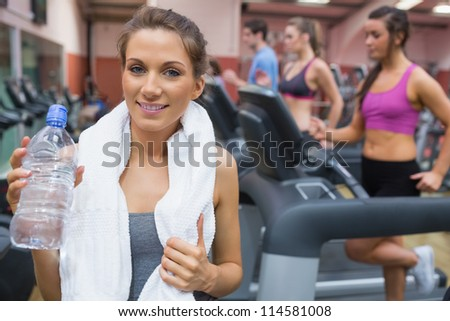 Woman smiling and drinking water in the gym - stock photo