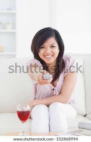 Woman smiling and holding a television remote in a living room