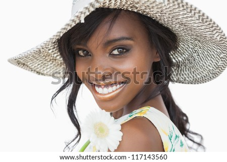 Woman smiling and holding white flower in a sun hat against white background
