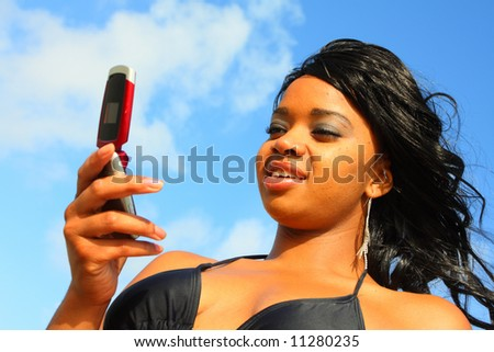 Woman smiling and looking at her phone - stock photo