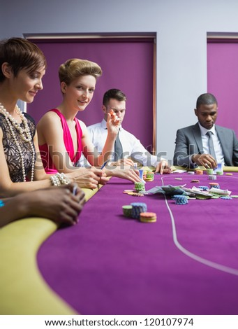 Woman smiling and looking up from poker game in casino - stock photo