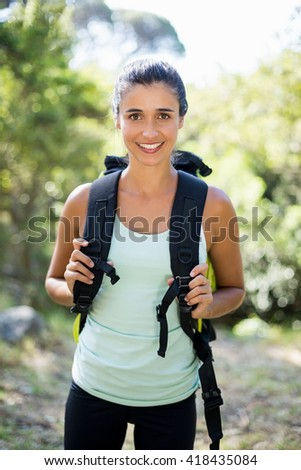 Woman smiling and posing with a backpack on the wood - stock photo