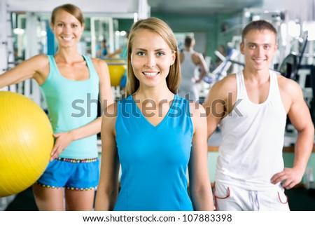 Woman smiling and standing in front of a group of gym people - stock photo