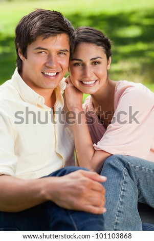 Woman smiling as she leans on her friend's shoulder while they are both sitting on grass in a park - stock photo
