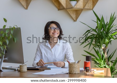 Woman smiling at office during working day - stock photo