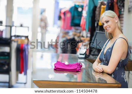 Woman smiling behind counter with folded clothes in clothing store - stock photo