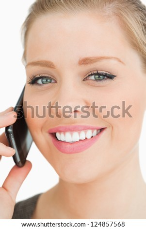 Woman smiling calling with her smartphone against white background