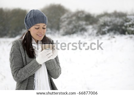 Woman smiling holding hot drink outside in the snow - stock photo