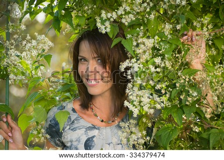Woman smiling in a park flowering plants