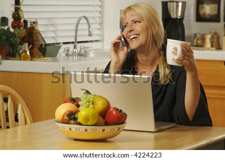 Woman smiling, in her kitchen on cell phone sitting in front of laptop. - stock photo