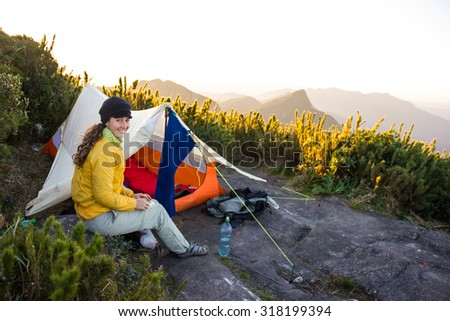 Woman smiling near the tent on the top of a Mountain in Brazil - stock photo