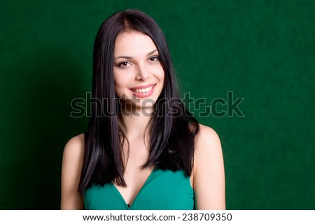 Woman smiling on green background.Young brunette girl portrait.Happy female. Surprised smiling attractive caucasian gir and a lot of copyspace. Natural looking cute person. Anadorned beauty,no make-up - stock photo