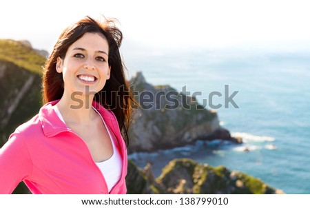 Woman smiling on nature coast landscape background. Happy beautiful brunette girl enjoying the view on summer travel in Asturias, Spain. - stock photo