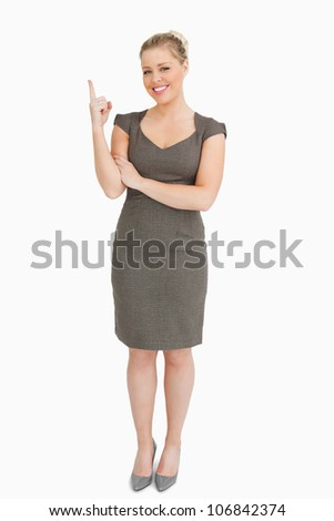 Woman smiling showing something with her finger against white background - stock photo