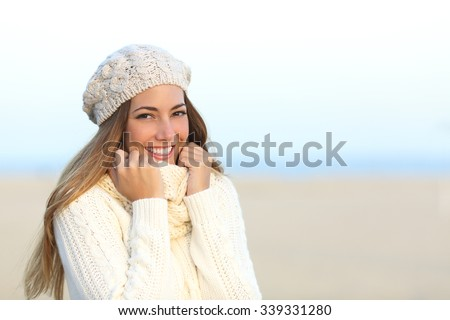 Woman smiling warmly clothed in a cold winter on the beach - stock photo