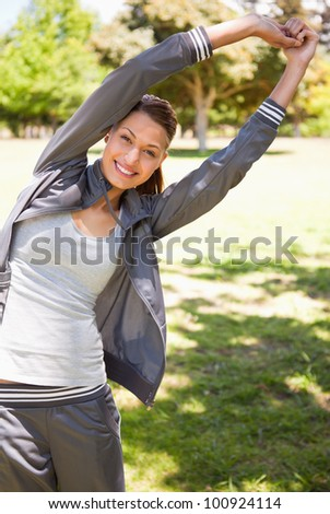Woman smiling while  doing overhead stretches as she is standing in the grass - stock photo