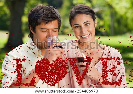 Woman smiling while her friend is drinking wine against love spelled out in petals - stock photo