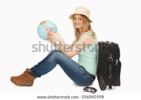 Woman smiling while holding a world globe against white background - stock photo