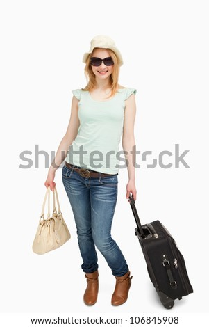 Woman smiling while holding luggages against white background - stock photo