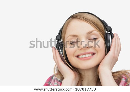 Woman smiling while listening music against a white background - stock photo