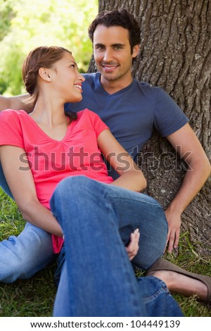 Woman smiling while looking at her friend as they sit together against the trunk of a tree