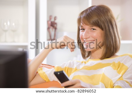 woman smiling while watching television at home