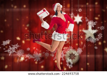 Woman smiling with christmas present against blurred christmas background - stock photo