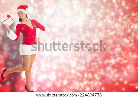 Woman smiling with christmas present against blurred lights - stock photo