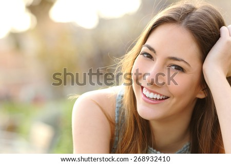 Woman smiling with perfect smile and white teeth in a park and looking at camera - stock photo