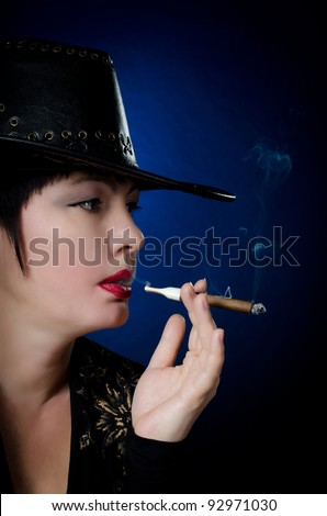 Woman smokes cigar portrait on a blue background - stock photo