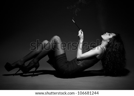 woman smokes in the dark. studio shot. space for text. BW Image - stock photo