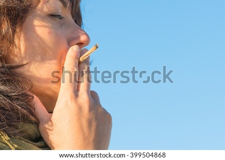 Woman smoking a cigarette joint - stock photo
