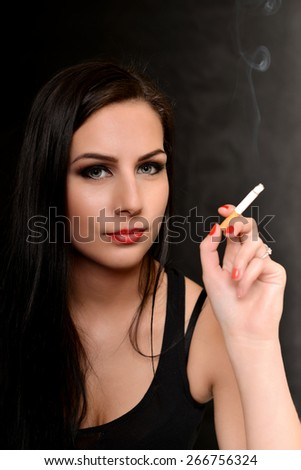 Woman Smoking a Cigarette  on Black Background - stock photo