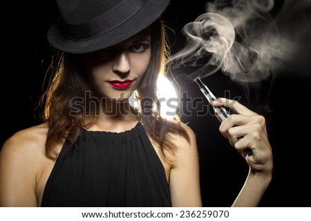 woman smoking or vaping an electronic cigarette to quit tobacco - stock photo